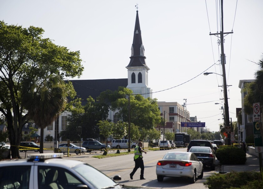 The steeple of Emanuel AME Church in Charleston, S.C., rises above the street as a police officer tells a car to move as the area is closed off after June's deadly shooting.