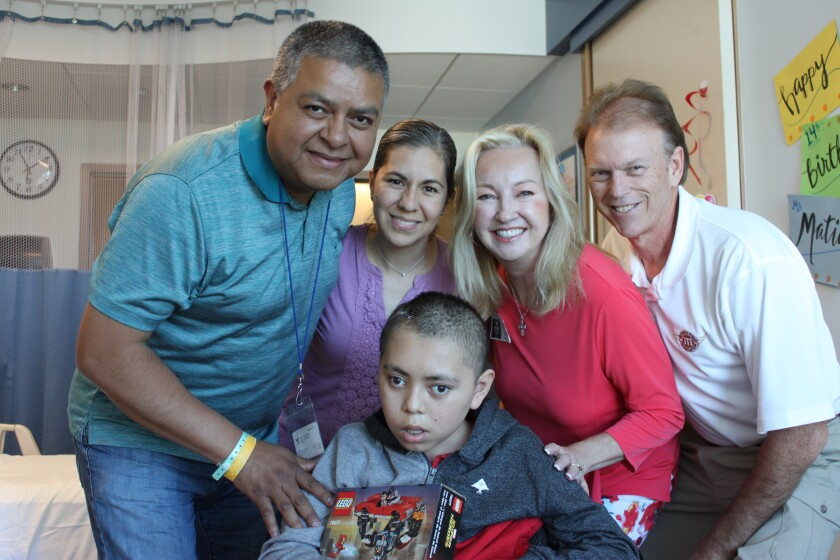 Beth and Brad Thorp (right) with a family in need due to their son's illness. The Mitchell Thorp Foundation helped provide support for the family.