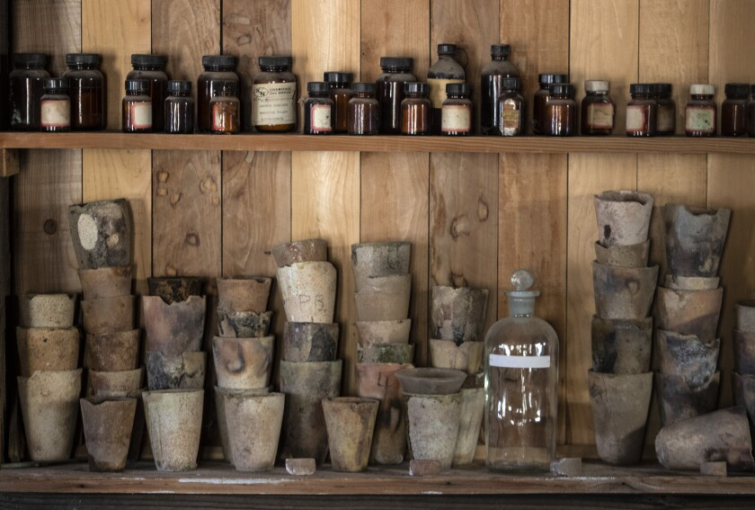 Vintage chemical jars and crucibles on a shelf at the Cerro Gordo ghost town in the Inyo Mountains