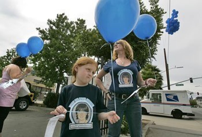 Amber Dubois' sister Allison (center) and their mother, Carrie McGonigle, prepared to release balloons with information on the missing teenager. (Peggy Peattie / Union-Tribune)
