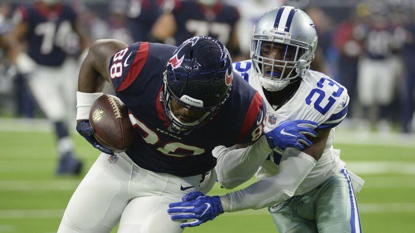Cowboys defensive back Tyree Robinson (right) tackles Texans tight end Jordan Akins.