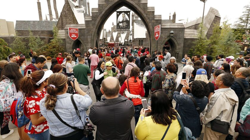Guests at Universal Studios Hollywood look into the front gate to the Wizarding World of Harry Potter attraction that opened in April 2016.