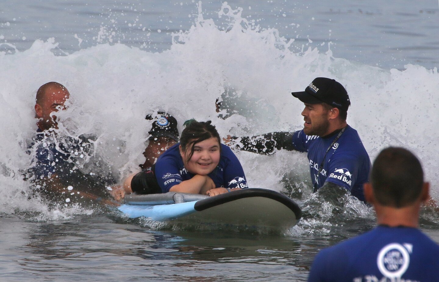 Mercy Hill-Mariscal, 12, of Huntington Beach, surfs with the assistance of volunteers. She injured her spine in a car accident when she was 2.