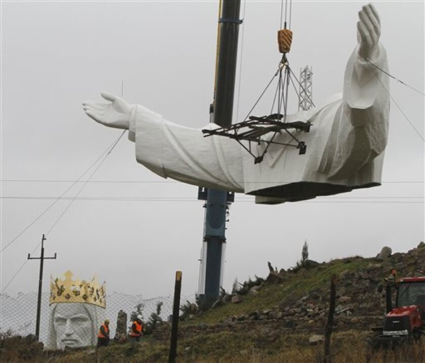 Workers raise the shoulders and arms of a statue of Jesus before placing them onto the figure's body, in Swiebodzin, Poland, on Saturday Nov. 6, 2010. A local priest is building what he claims to be the largest statue of Jesus Christ in the world. (AP Photo/Czarek Sokolowski)