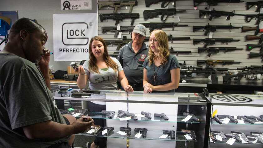 At the Get Loaded gun store in Grand Terrace, store managers Jamie Taflinger, left, and Kendyll Murray show customer Cornell Hall of Highland different types of ammo.