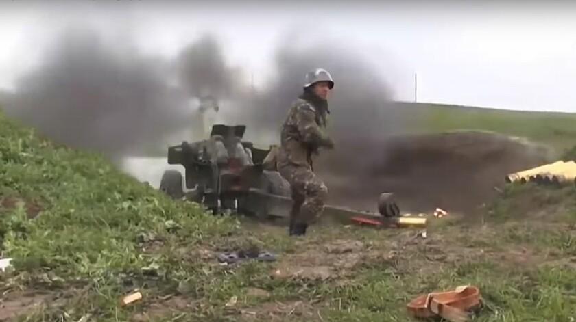 An Armenian serviceman fires a cannon toward Azerbaijani positions in Nagorno-Karabakh.