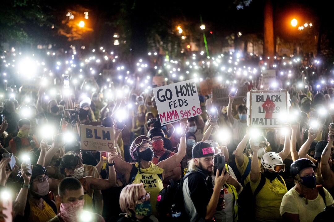Hundreds of protesters hold their phones aloft on Monday in Portland, Ore.
