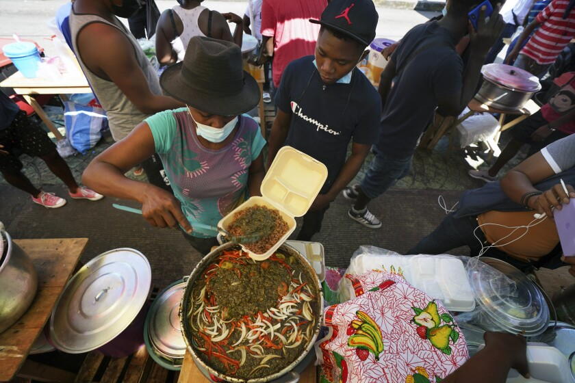 In this Sept. 3, 2021 file photo, a Haitian vendor sells traditional food outside a market in Tapachula