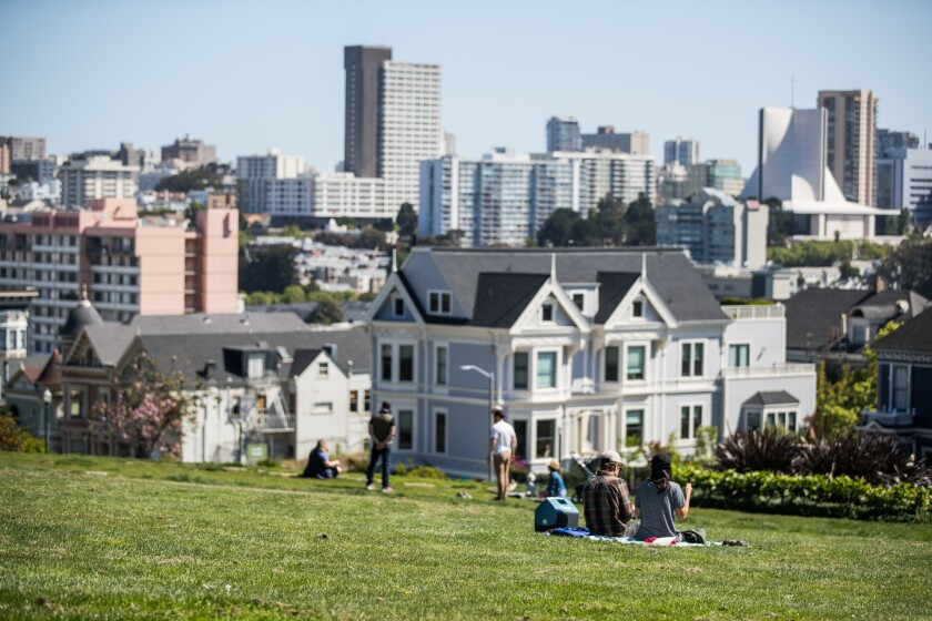 People sit on the grass at San Francisco's Alamo Square Park during the pandemic.