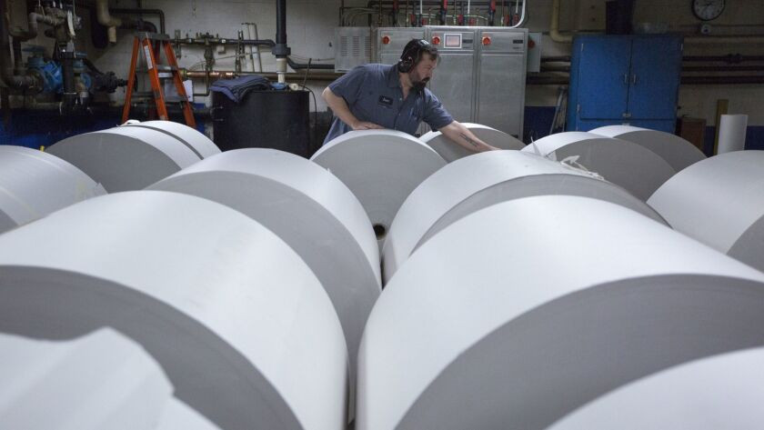Jason Campbell adjusts rolls of newsprint before printing at the Columbian newspaper in Vancouver, Wash.