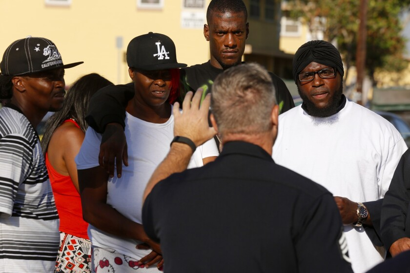 An LAPD officer addresses a group in Nickerson Gardens, where an investigation is underway into a gun battle with Los Angeles police that left an 18-year-old dead and one officer wounded.