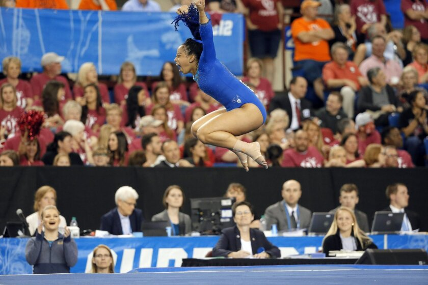 FILE - In this April 16, 2016, file photo, UCLA's Sophina DeJesus celebrates after her floor exercise routine during the NCAA women's gymnastics championships in Fort Worth, Texas. DeJesus managed to do something this year that three-time world champion Simone Biles, reigning Olympic champion Gabby