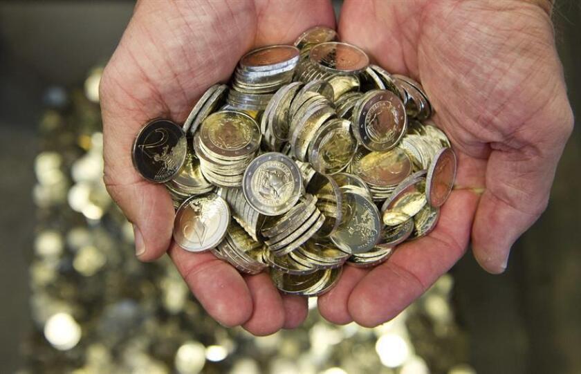 Un hombre sostiene varias monedas de euro. EFE/Archivo