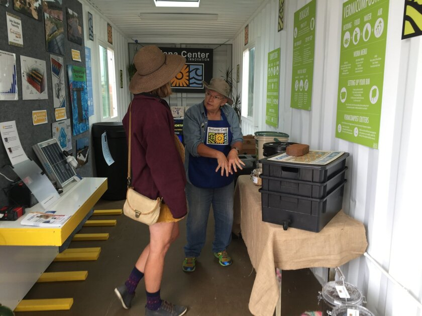 Judi Heitz, a volunteer with Solana Center for Environmental Innovations describes to a fair visitor how micro-organisms in the Bokashi Bran Bucket system can break down chicken bones. Worm composting bins and other equipment also are housed inside the center's new Eco-Container.