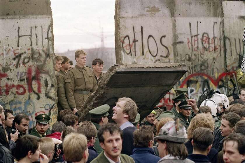 A crowd in West Berlin watches East German border guards demolish the Berlin Wall near Potsdamer Platz in November 1989.