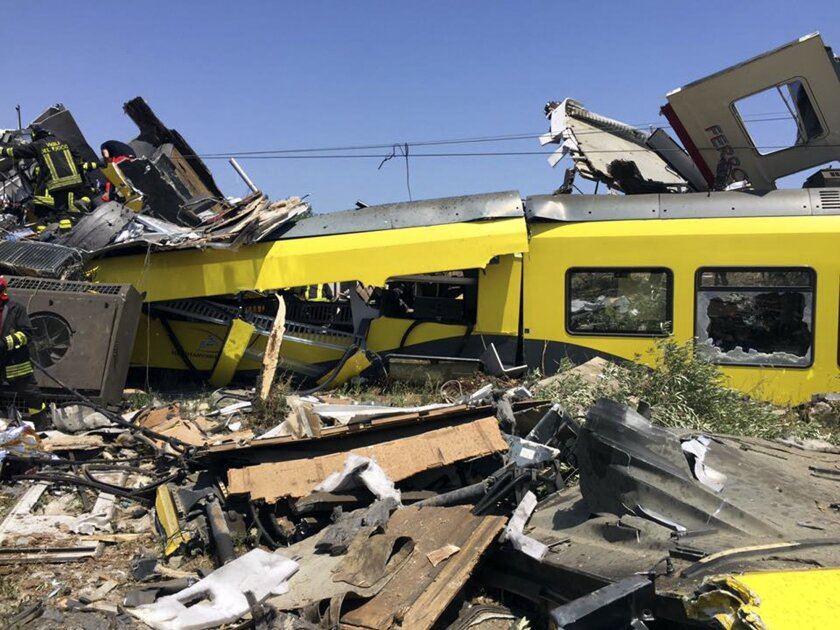 Italian firefighters search among debris at the scene of a train accident after two commuter trains collided head-on near the town of Andria, in the southern region of Puglia, killing several people, Tuesday, July 12, 2016.  (Massimo Mazzilli via AP)