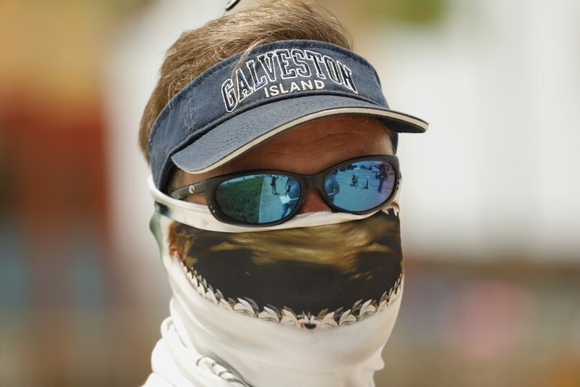 Raymond Smith, owner of Duck Tours on Galveston Beach, wears a shark scarf on his face.
