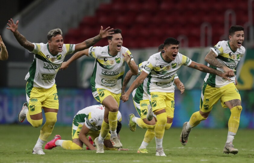 Players of Argentina's Defensa y Justicia celebrate after winning the Recopa Sudamericana final soccer match against Brazil's Palmeiras in a penalty kick shoot-out at the Mane Garrincha stadium in Brasilia, Brazil, Wednesday, April 14, 2021. (Ueslei Marcelino/Pool via AP)