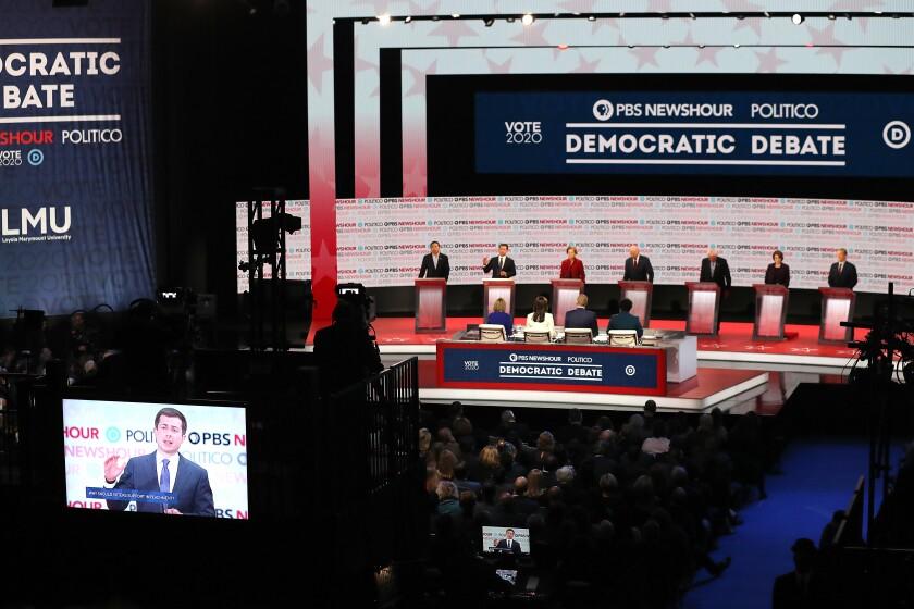 Pete Buttigieg speaks as former Andrew Yang, Elizabeth Warren, Bernie Sanders, Amy Klobuchar and Tom Steyer, from left, listen during the Democratic presidential primary debate in Los Angeles.