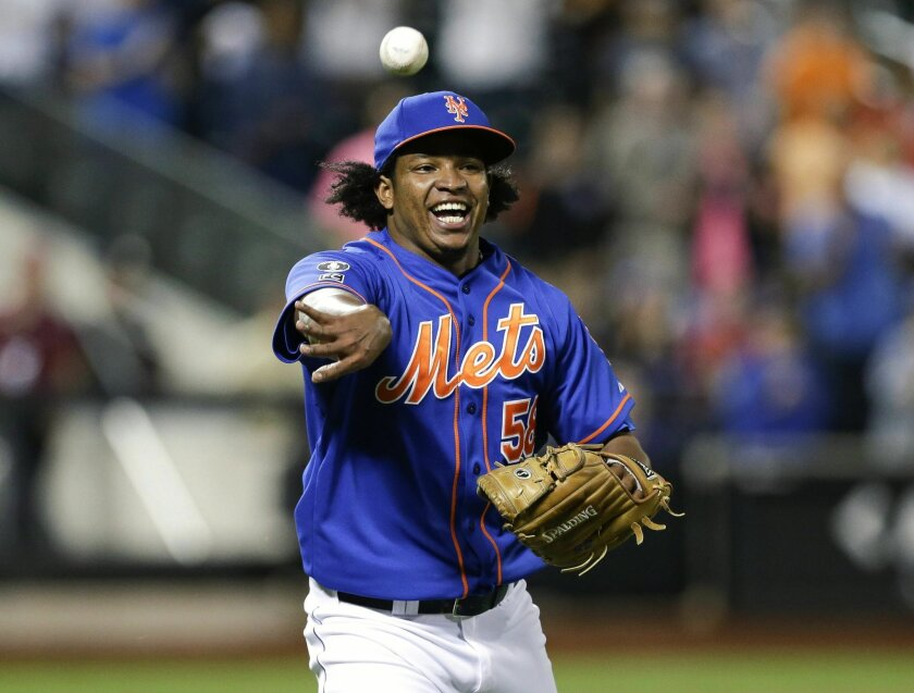 FILE - In this Wednesday, Sept. 10, 2014, file photo, New York Mets relief pitcher Jenrry Mejia tosses the ball to throw out Colorado Rockies' Josh Rutledge at first base to end a baseball game in New York. Mejia became the first player to receive a lifetime ban under baseball's drug agreement test