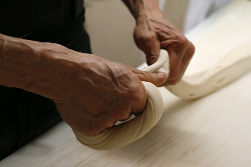 """Bagel maker Sam Ung rolls dough into a bagel in the basement of Ess-a-Bagel, Thursday, May 26, 2016, in New York. Ess-a-Bagel's holes are small but the bagels are big. The large size is somewhat of an accident after the family found a baker who shared his recipe, COO Melanie Frost said. """"They put t"""