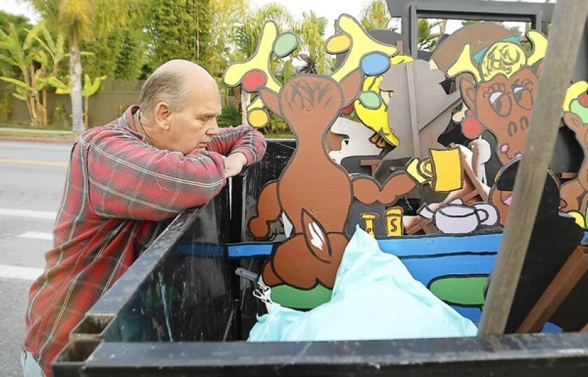 """Jim Jordan leans on his truck full of the reindeer cutouts and other props used in his Costa Mesa home's popular annual Christmas display. The home is nicknamed the """"Snoopy House."""" He was forced to remove the set pieces Tuesday because the bank had foreclosed on the home."""