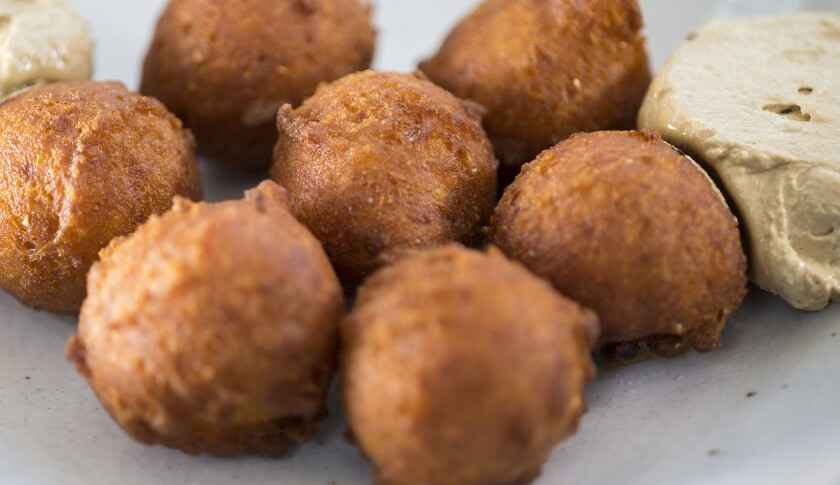 Hush puppies are served with molasses butter at Manuela, a restaurant in the middle of the Hauser &