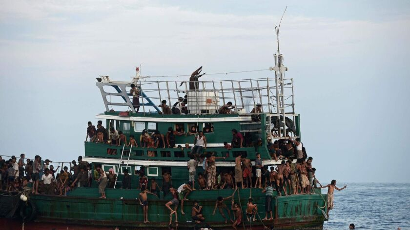 Rohingya migrants bring back food supplies dropped by a Thai army helicopter after jumping into the sea to collect them.
