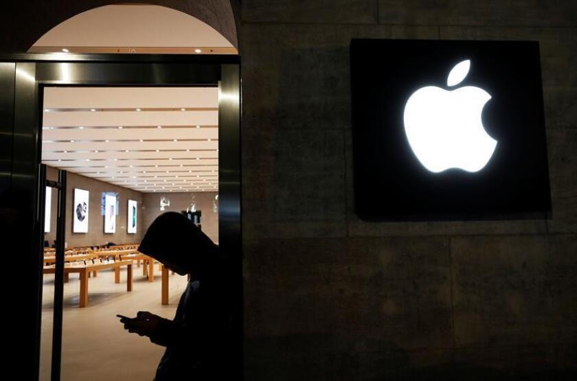 Un cliente mira su dispositivo móvil mientras espera para el lanzamiento del nuevo iPhone X de Apple frente a una tienda Apple. EFE/Archivo