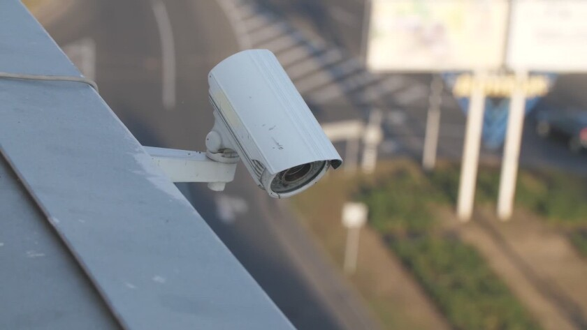A surveillance camera on the side of a building.