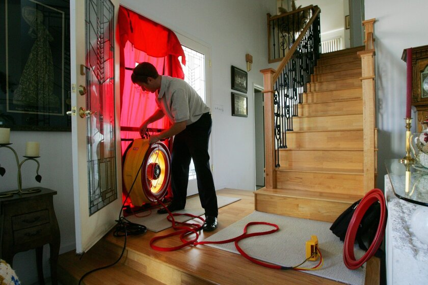 John Adkins of Get Green Remodeling, installs a blower door to measure air leaks during a home energy audit in the Del Cerro neighborhood last month.