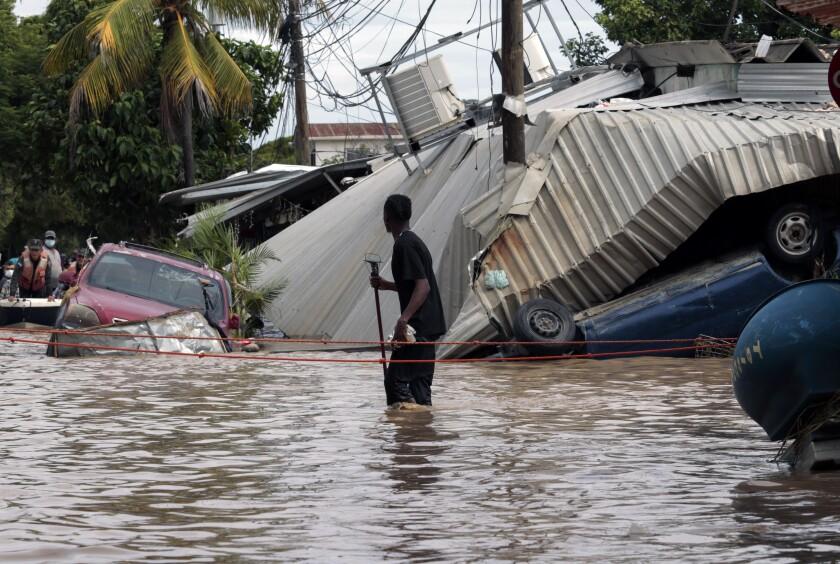 En esta foto de archivo del 6 de noviembre de 2020, un residente que camina por una calle inundada
