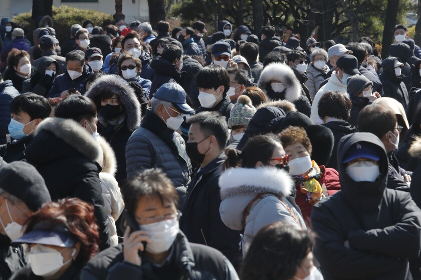People line up outside Nonghyup Hanaro Mart in Seoul on Thursday to buy face masks to protect themselves from the coronavirus.
