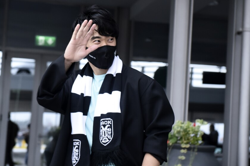 Japanese soccer player Shinji Kagawa waves upon his arrival at the airport in Thessaloniki, Greece, Tuesday, Jan. 26, 2021. Former Manchester United and Borussia Dortmund midfielder Shinji Kagawa has moved to PAOK based in the northern Greek city of Thessaloniki, the soccer club announced on Wednesday, Jan. 27, 2021. (AP Photo/Giannis Papanikos)