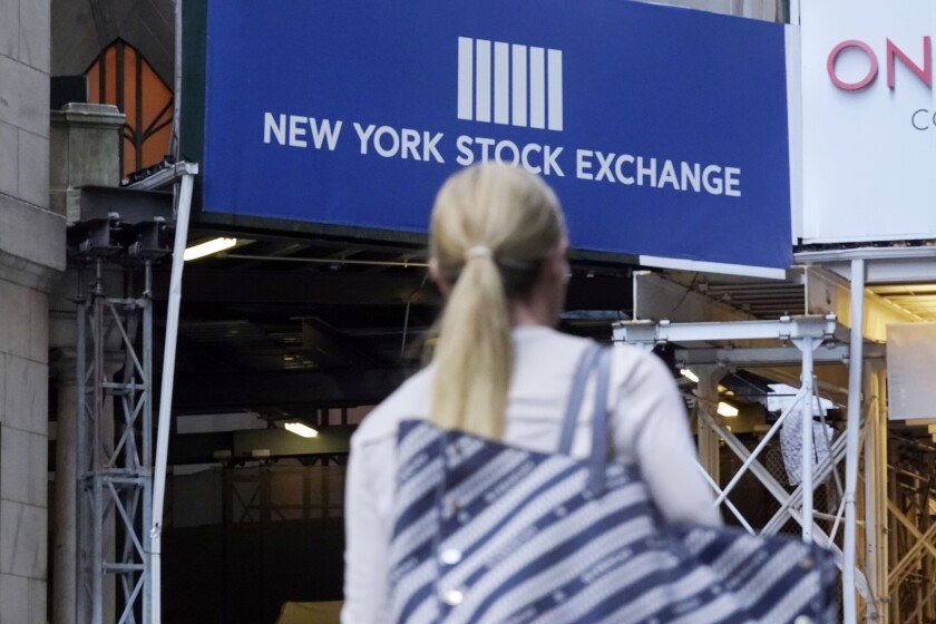 A woman passes an entrance of the New York Stock Exchange.