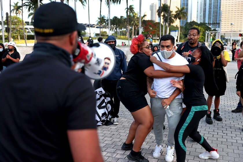 A man is held back from attacking a man using a bullhorn
