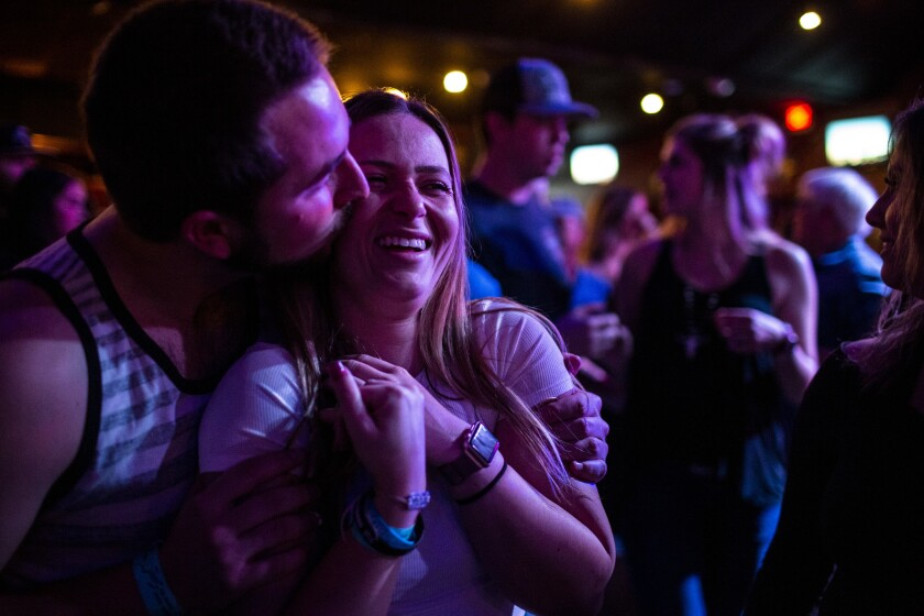 Harrison King, 24, of Thousand Oaks kisses his girlfriend, Alexis Tait, 23, of Simi Valley before hitting the dance floor for line dancing Thursday at Borderline Country Night at The Canyon bar.