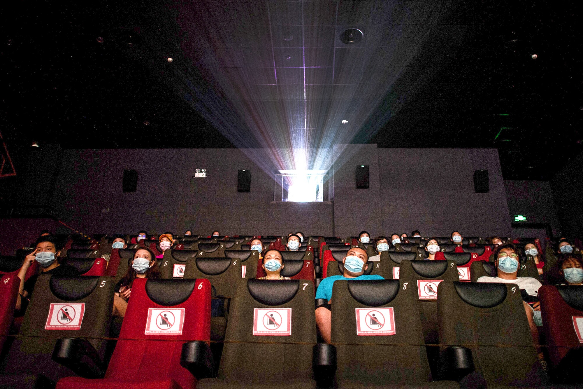 People in masks watch a movie, sitting apart to ensure social distancing.