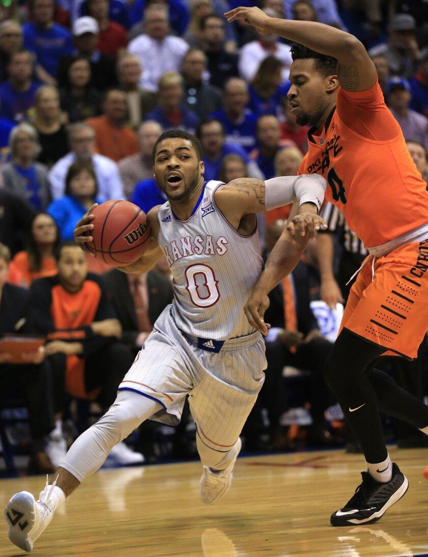 Kansas guard Frank Mason III (0) drives on Oklahoma State guard Joe Burton (4) during the first half of an NCAA college basketball game in Lawrence, Kan., Monday, Feb. 15, 2016. (AP Photo/Orlin Wagner)