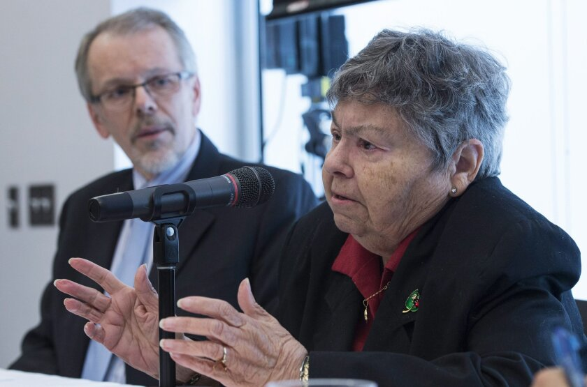 Lise Blais, whose Jean-Yves Blais, who died from lung cancer which developed from smoking, makes a statement as Mario Bujold, executive director of the Quebec Tobacco and Health Council listens during a news conference Monday, June 1, 2015, in Montreal. A judge has awarded more than $15 billion Can