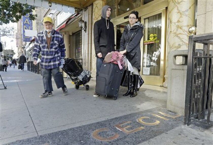 A man, left, leaves the Cecil Hotel with belongings as Michael and Sabina Baugh, both 27, of Plymouth, England, wait for transportation as they leave the hotel in downtown Los Angeles Wednesday, Feb. 20, 2013.  Early Tuesday, police discovered the body of a Canadian woman at the bottom of the histo