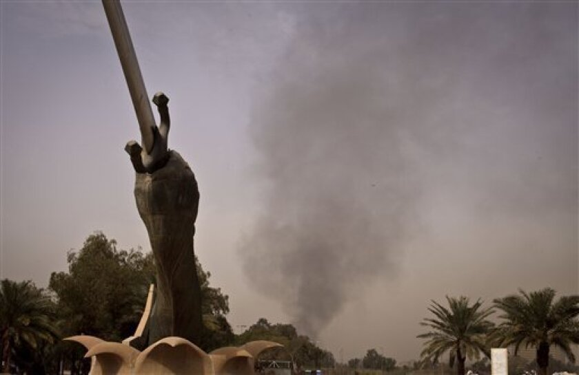 Black smoke from a car bomb attack is seen from the the Cross Words monument in Baghdad, Iraq, Thursday, March, 14, 2013. A string of explosions tore through central Baghdad within minutes of each other on Thursday, followed by what appeared to be a coordinated assault by gunmen who battled security forces in the Iraqi capital, according to officials. Authorities say several people have been killed. (AP Photo/Maya Alleruzzo)