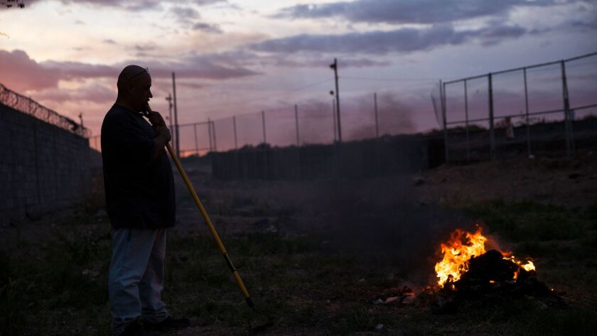 A man burns trash near the border fence in Ciudad Juarez, Mexico, last month.