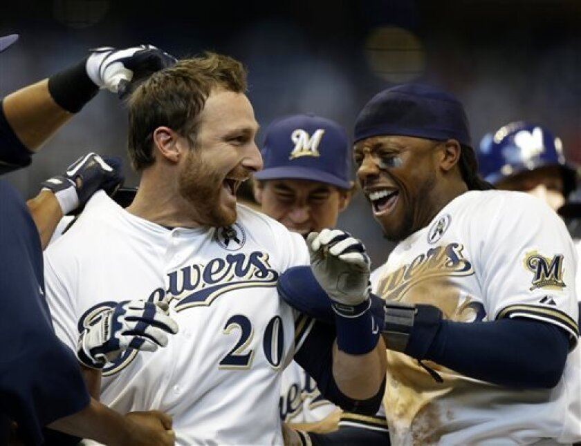 Milwaukee Brewers' Jonathan Lucroy, left, celebrates with Rickie Weeks, right, and other teammates after Lucroy's game-winning sacrifice fly against the Colorado Rockies in the 11th inning of an opening day baseball game on Monday, April 1, 2013, in Milwaukee. The Brewers won 5-4. (AP Photo/Jeffrey