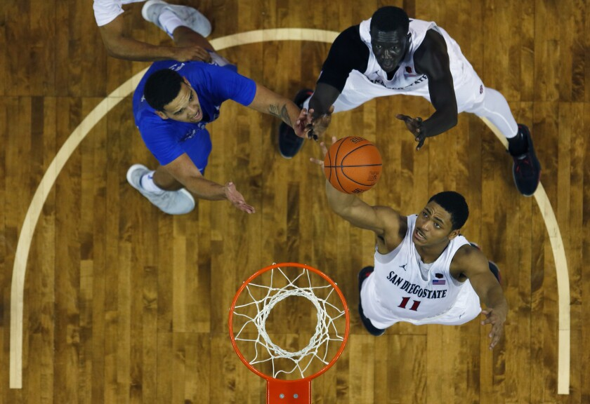 SDSU's Matt Mitchell (11) and Aguek Arop battle for a rebound in the Mountain West tournament last March.