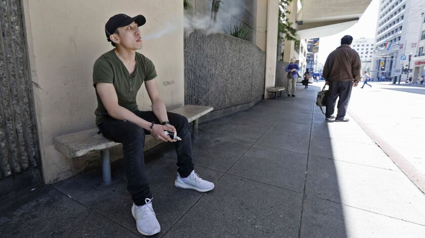 In this Monday, June 17, 2019, photo, Jacky Chan, 23, takes a vaping break from his job at a smoke s