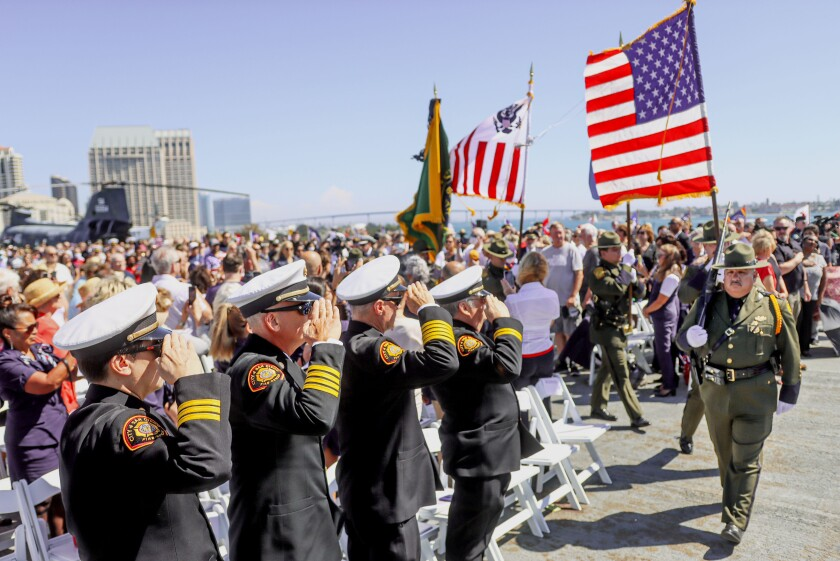 Attendees of a 9/11 memorial ceremony salute at an American flag carried by an honor guard