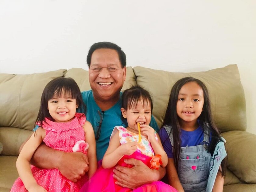 A family photo of a man and his three granddaughters on a couch