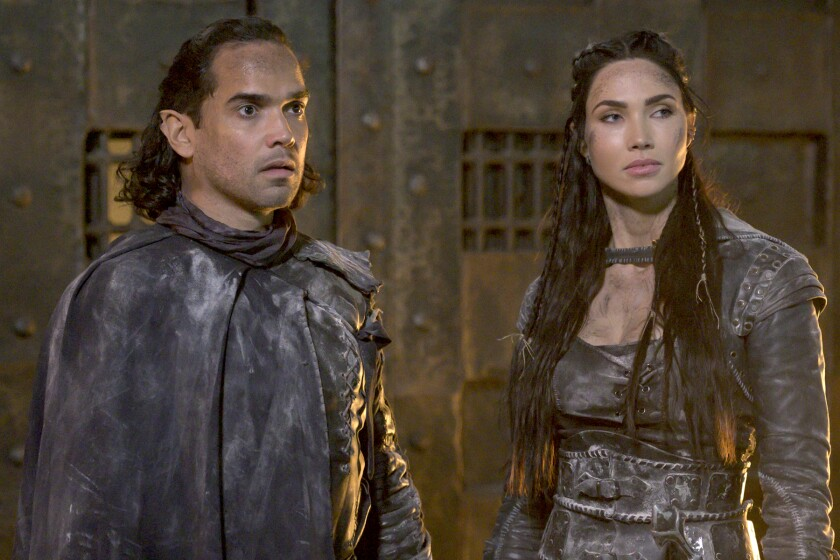 """A man and a woman in brown futuristic leather outfits in """"The Outpost"""" on The CW."""