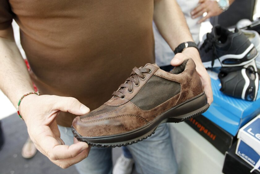 A man shows a shoes in a market in Catania, Sicily, southern Italy, Friday, May 8, 2015. When migrants arrive in Italy, exhausted after days of perilous travel in overcrowded boats, one of the first things they receive is a pair of shoes. The gleaming sneakers stand out incongruously against the migrants' clothes, grimy and threadbare from days of travel. (AP Photo/Antonio Calanni)